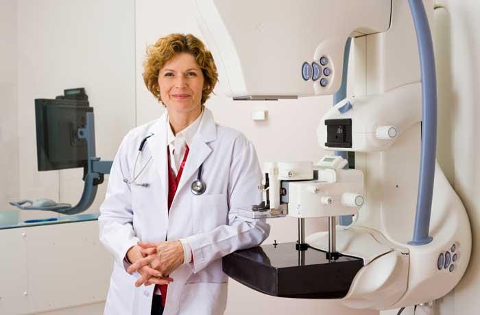 Doctor sonriente en sala de mamografías